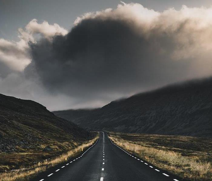 Open road with dark storm clouds in the distance