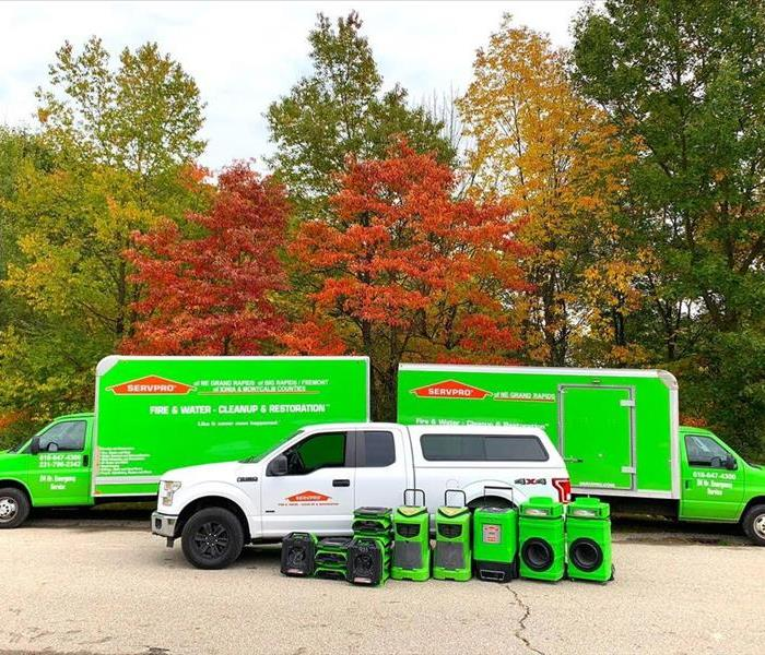 Multiple SERVPRO vehicles lined up against fall trees
