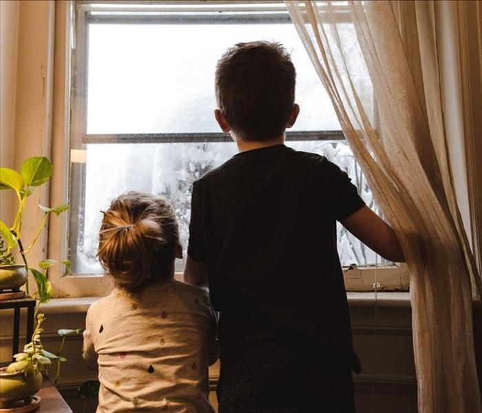 Two little boys looking out the window
